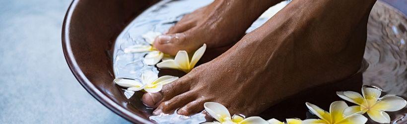 Bain de pieds dans de l'eau avec des fleurs pour se relaxer
