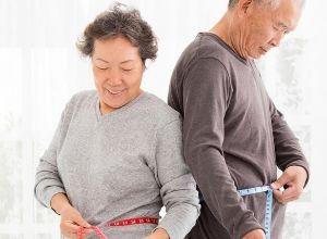 Couple de seniors qui prennent des mesures au niveau de leur ventre