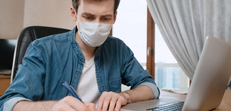 Jeune homme qui passe son examen en ligne depuis chez lui en vue de la situation de crise de la COVID-19
