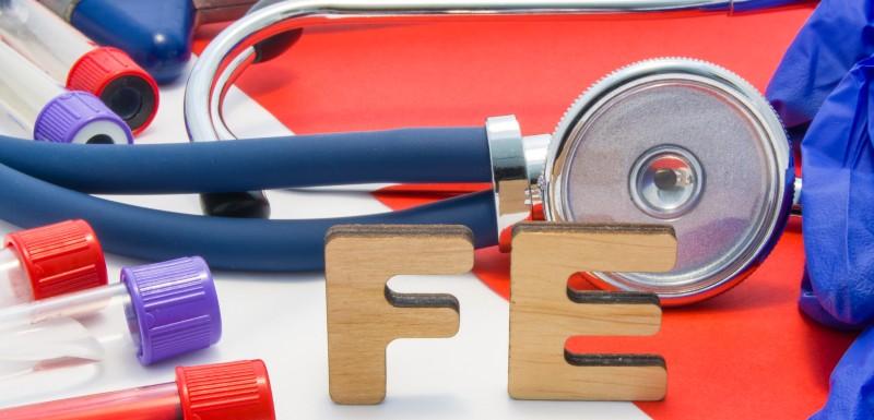 FE (fer) en lettre de bois entouré de tubes à essai avec du sang, stéthoscope et autre instruments médicaux