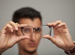 Homme qui tient sa paire de lunettes dans ses deux mains devant lui