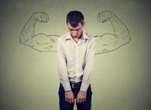 Jeune homme la tête baissé et les bras tombant le long du corps devant un dessin de bras musclés