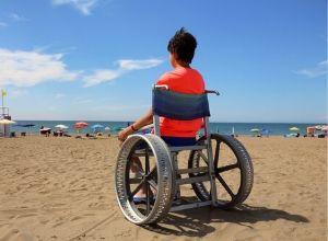 Jeune homme en fauteuil roulant à la plage