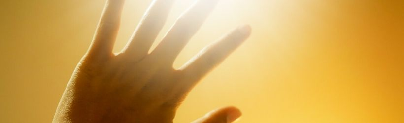 Main vers le ciel se protégeant de la lumière du soleil