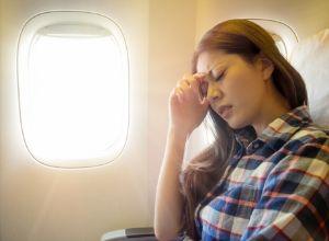 Femme assise dans un avion, près du hublot, se protégeant de la lumière du jour
