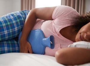 Femme allongée avec une bouillotte posée sur son ventre