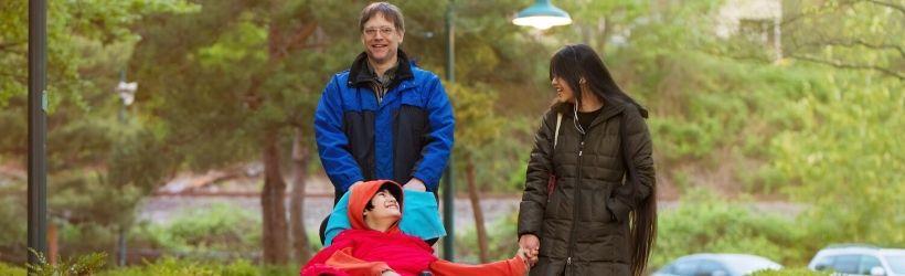 Enfant handicapé dans un fauteuil roulant poussé par son père et sa soeur