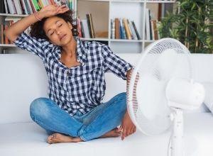 Femme devant son ventilateur pour supporter la chaleur