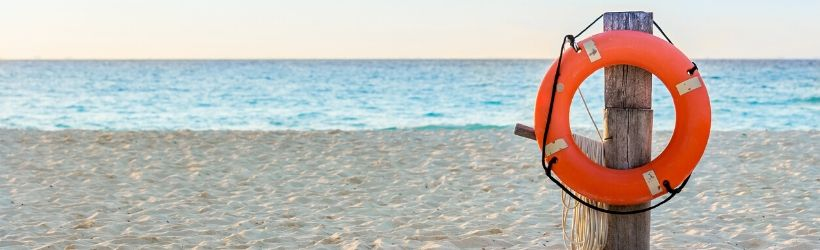Bouée de sauvetage accrochée à un poteau de bois sur la plage