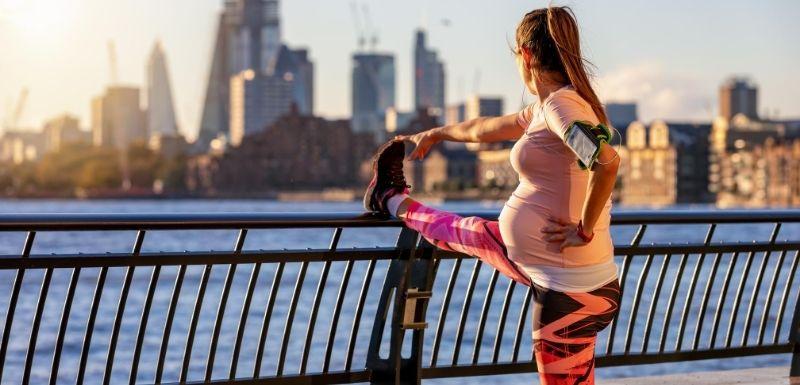 Femme enceinte fait ses étirements après avoir couru