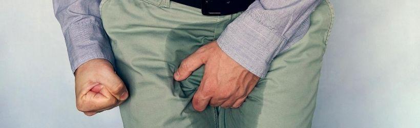Homme qui se tient la partie intime ayant eu des pertes dans son pantalon