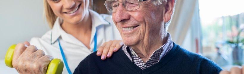 Infirmière qui aide un homme âgé à employer la bande de résistance