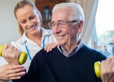 Infirmière qui aide un homme âgé à domicile à utiliser un elastique pour se remuscler