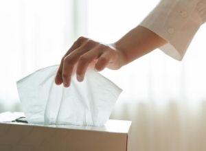 Femme qui sort un mouchoir de la boîte à mouchoir