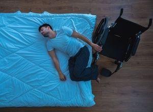 homme qui est allongé sur le lit, son fauteur roulant se trouve à côté de lui