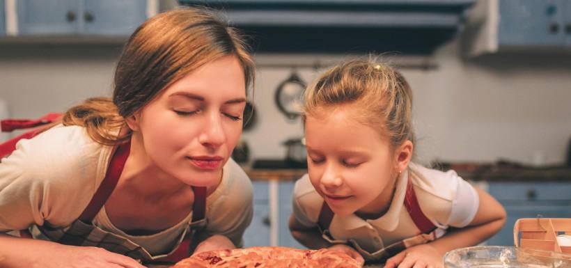 une femme et sa fille qui sentent un gâteau