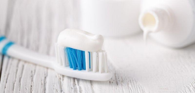 tube dentifrice, avec au premier plan une brosse à dent avec une noisette de pâte à dentifrice dessus
