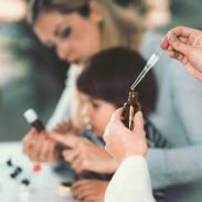 mère qui montre à son enfant un flacon d'homéopathie pendant qu'un médecin prélève du liquide avec une pipette