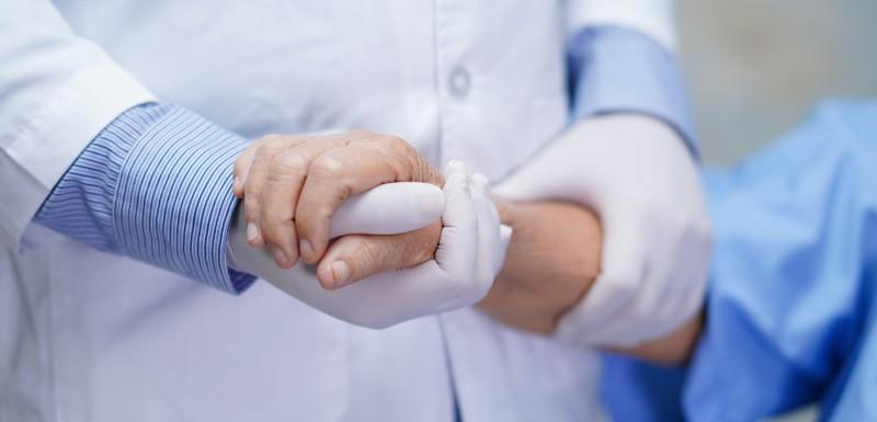 main d'une patiente recouverte par une main d'un médecin d'hopital