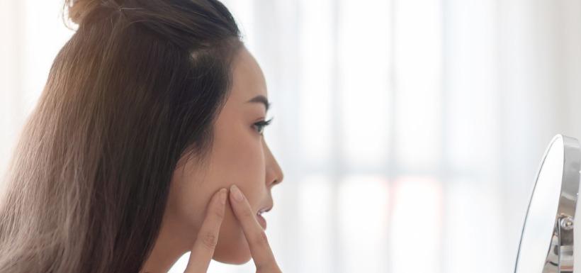 Une femme touchant un bouton d'acné devant un miroir