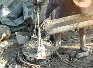 un ouvrier sur un chantier faisant couler du béton