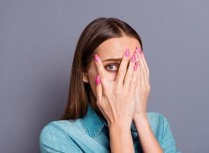 femme qui se cache les yeux car elle a peur
