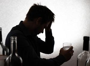 un homme dans le noir avec un verre d'alcool