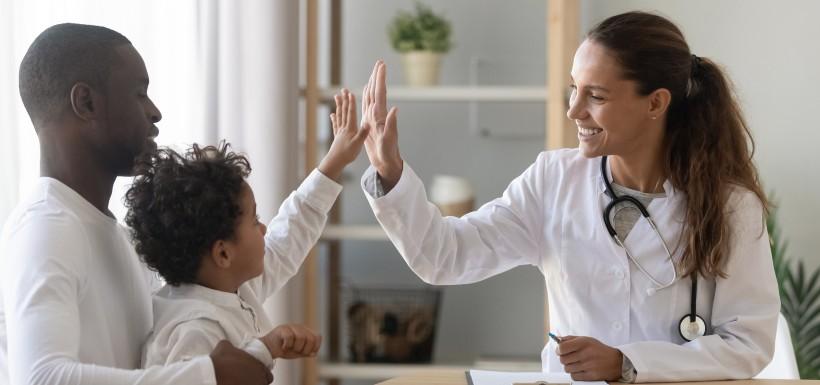 une médecin et un enfant qui se tapent dans la main