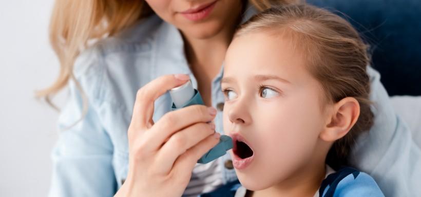 femme qui introduit un inhalateur dans la bouche de sa petite fille