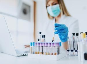 femme avec un masque prenant un tube à essai dans un laboratoire