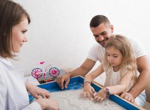 une enfant jouant avec du sable autour des ses parents