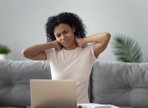 une femme se touchant le cou devant son ordinateur