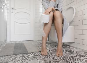 une femme assise au toilettes avec un rouleau de papier