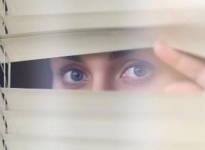 Femme qui regarde discrètement par la fenêtre