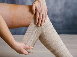 personne qui met un pansement sur son ulcère de la jambe