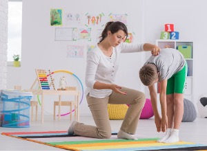 Femme qui aide un garçon à faire des exercice musculaires